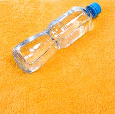 Water In Bottle On Orange Towel Royalty Free Stock Photography