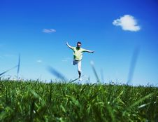 Free Jumping Up Guy In A Green Shirt Against Blue Sky. Stock Images - 15305914