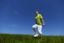Jumping Up Guy In A Green Shirt Against Blue Sky. Stock Image