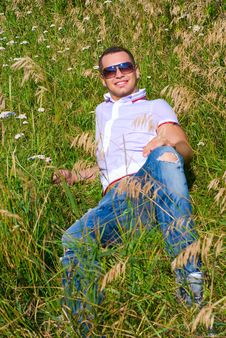 Happy Young Man In Grass Stock Photo