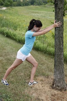 Young Woman Stretching On A Tree Stock Photo