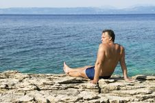 Free Man Sunbathing On Rocks Royalty Free Stock Photo - 15333205