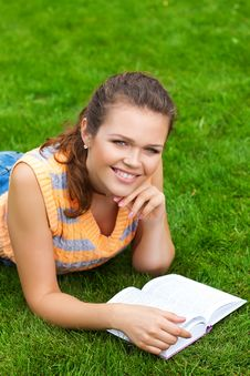 Girl On Grass With Book Stock Photography