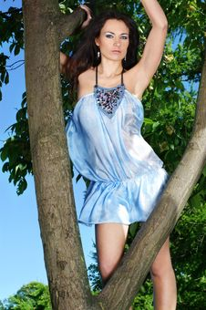 Young Brunette Girl Is Standing In A Blue Dress Royalty Free Stock Photo