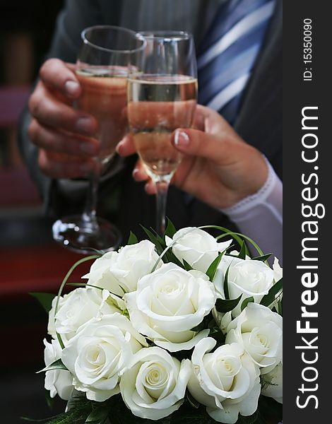 White roses and two hands holding goblets.