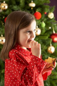 Free Girl Eating Star Shaped Cookie In Front Of Tree Stock Photography - 15377302