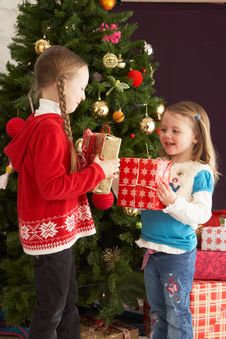 Two Young Girls With Presents In Front Of Tree Royalty Free Stock Images