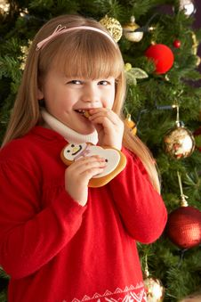 Free Girl Eating Cookie In Front Of Christmas Tree Stock Photos - 15378383