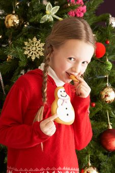 Free Girl Eating Cookie In Front Of Christmas Tree Royalty Free Stock Photo - 15378405
