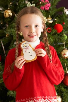 Free Girl Eating Cookie In Front Of Christmas Tree Stock Photography - 15378472