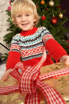 Young Boy Holding Gift In Front Of Christmas Tree Royalty Free Stock Images