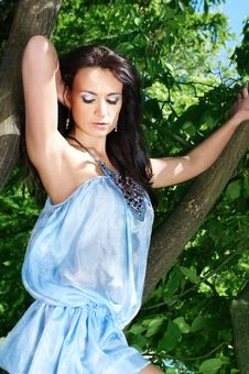 Young Brunette Girl Is Standing In A Blue Dress Stock Images