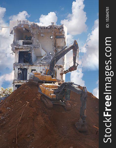 Tractors destroying a building