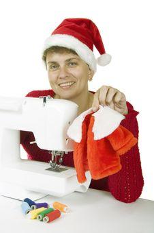 Woman Sewing A Fur Coat For Santa Claus Stock Photo