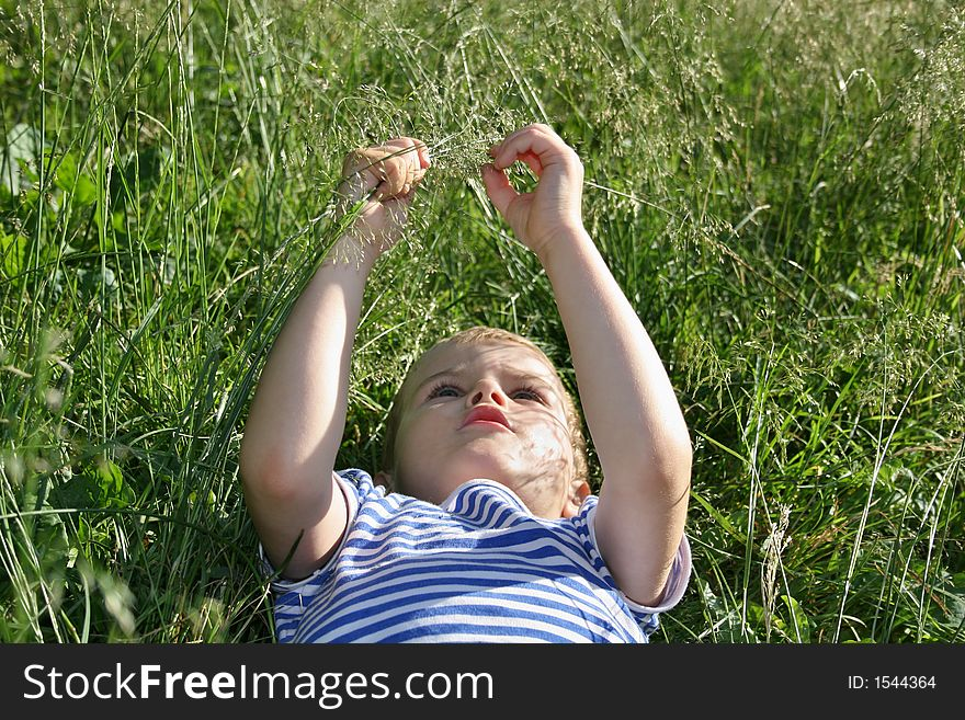 Kid head lies on grass