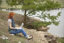 Girl With Laptop At Rock Near Lake And Tree. Royalty Free Stock Images