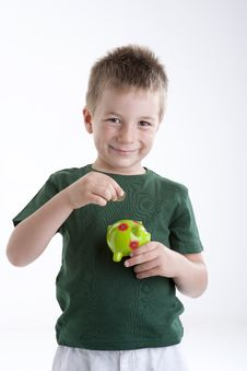 Little Boy Depositing Money In His Piggy Bank. Stock Photography