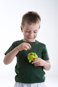Free Little Boy Depositing Money In His Piggy Bank. Royalty Free Stock Photography - 15409697