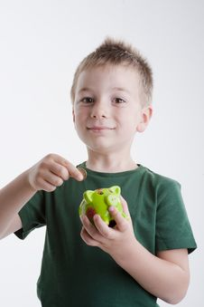 Free Little Boy Depositing Money In His Piggy Bank. Royalty Free Stock Photography - 15409747