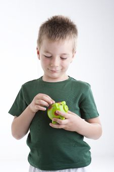 Little Boy Depositing Money In His Piggy Bank. Stock Photos