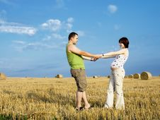 Young Pregnant Woman With Husband In The Meadow Stock Photography