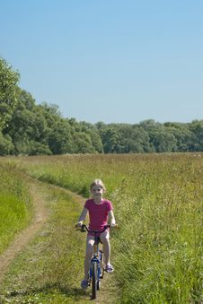 Little Girl On Bicycle On Meadow Stock Images