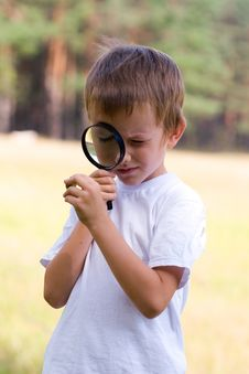 Happy Boy With A Magnifying Glass Stock Photos