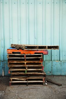 Free Colorfully Painted Wooden Pallets By A Blue Wall Stock Photo - 15481350