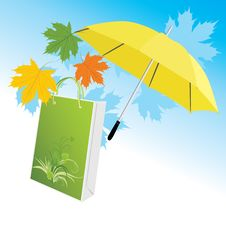 Yellow Umbrella With Package And Maple Leaves Stock Photo