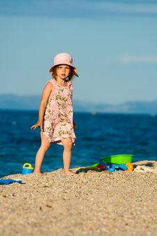 Little Beautiful Girl Goes On The Beach. Stock Photos