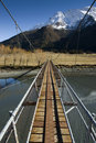Free Swing Bridge Crossing To Snow Capped Mountains Royalty Free Stock Image - 15508096