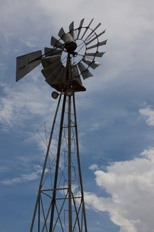 Rural Windmill Backlit Against Partly Cloudy Sky Stock Photos