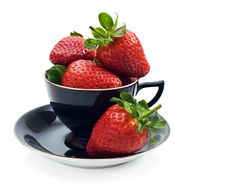 Strawberries In A Tea Cup Royalty Free Stock Photos