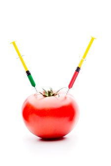 Syringe Injecting Red Green Liquid Into Tomato Royalty Free Stock Photos