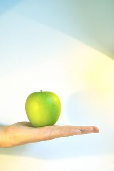Free The Green Apple Is At The Palm Against Colour Back Royalty Free Stock Photo - 15527725