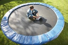 Young Man Relaxing On Trampoline With Laptop Stock Images