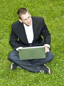 Young Businessman On The Grass With His Laptop Stock Photo