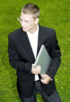 Free Young Businessman Standing On Grass With Laptop Royalty Free Stock Image - 15542736