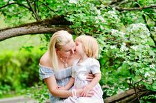 Girl Kiss Her Mother In Blooming Garden Royalty Free Stock Images