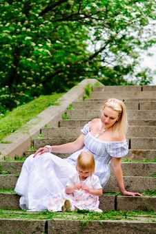 Woman And Her Baby Daughter Sit On A Stone Steps Royalty Free Stock Photography