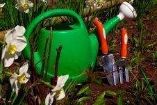 Green Watering Can With Gardening Equipment Behind Royalty Free Stock Photo