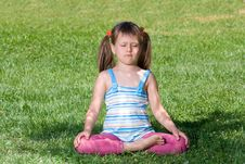 Free Little Child Sit And Meditate In Asana On Grass Royalty Free Stock Images - 15569109