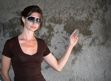 Young Pretty Woman Point The Finger At The Wall Royalty Free Stock Photography