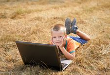 Free Young Boy Laying On Ground With Laptop Royalty Free Stock Photo - 15583405