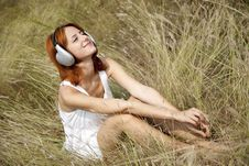 Beautiful Red-haired Girl At Grass With Headphones Royalty Free Stock Photos