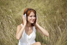 Beautiful Red-haired Girl At Grass With Headphones Stock Image