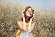 Beautiful Red-haired Girl At Grass With Headphones Royalty Free Stock Photography