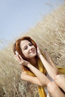 Beautiful Red-haired Girl At Grass With Headphones Stock Photo