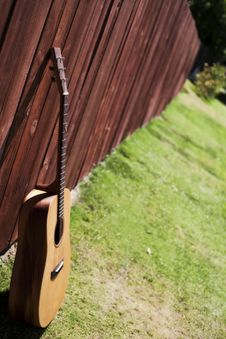 Free Guitar Against A Red Wood Fence Stock Images - 15661684