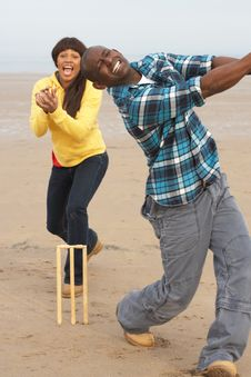 Young Couple Playing Cricket On Autumn Beach Holid Royalty Free Stock Photography